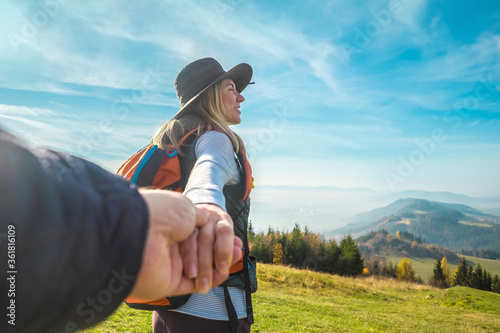 Obraz na plátně Happy traveler woman tourist stay on the green grass on the peak of mountain and look on the nice fog view