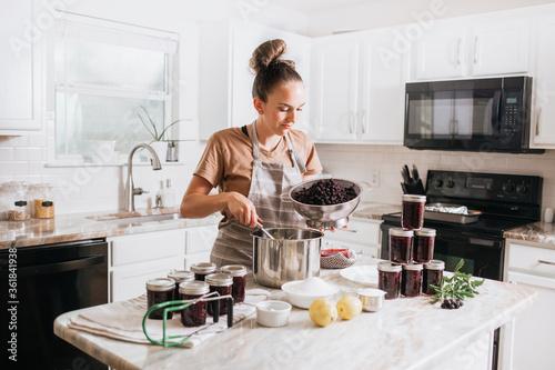 Valokuvatapetti Woman canning homemade blackberry jam in home kitchen