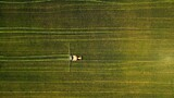 Birds-eye view of a tractor working in a green field