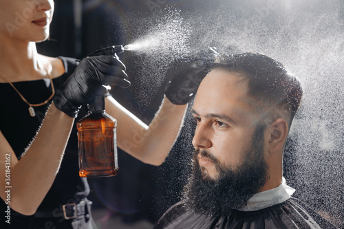 Fototapeta Woman barber cutting hair to a bearded man. obraz