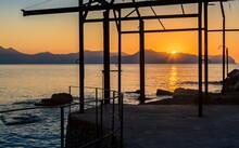 The Sun Dips Below The Mountai...