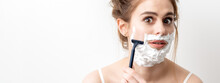Beautiful Young Caucasian Woman Shaving Her Face By Razor On White Background. Pretty Woman With Shaving Foam On Her Face