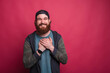Leinwandbild Motiv Touched greatful bearded hipster is holding hands together  to his chest smiling to the camera