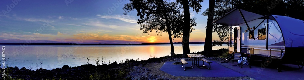 Fototapeta Travel trailer camping by the Mississippi river at sunset in Thomson Causway Illinois