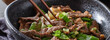 eating chinese beef and snowpeas stirfry in bowl with chopsticks