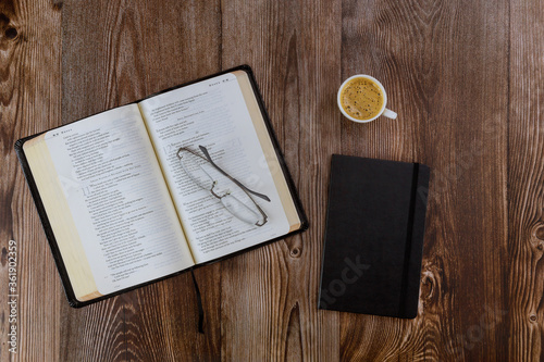 Fotografia, Obraz Open Bible lying on a wooden table in a reading the Holy Bible