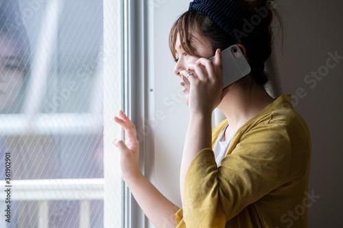 Fotografie, Obraz 窓から外を眺めながら電話をする女性