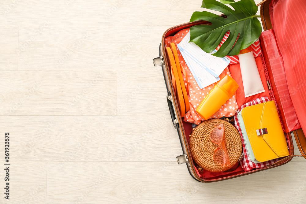 Fototapeta Packed suitcase on light background. Travel concept