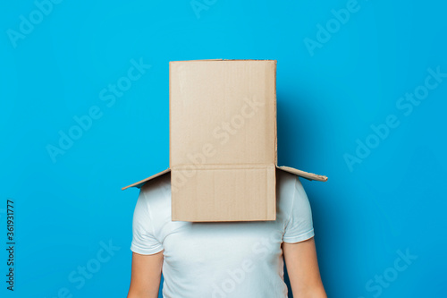 Fotomural Young man in a white T-shirt with a cardboard box on his head on a blue backgrou