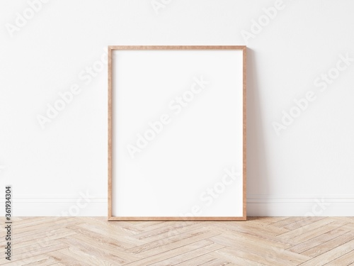 Vertical rose gold empty picture frame on wooden floor Canvas