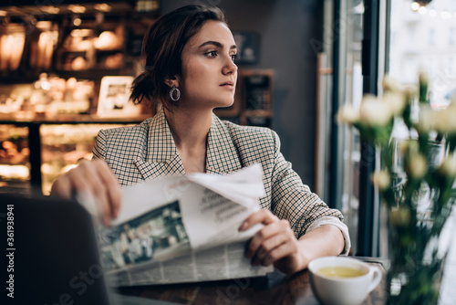 Pensive entrepreneur spending time for reading daily newspaper in morning, conte Canvas Print