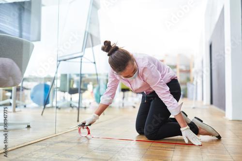 Fotomural Geschäftsfrau markiert Boden im Büro mit Klebeband