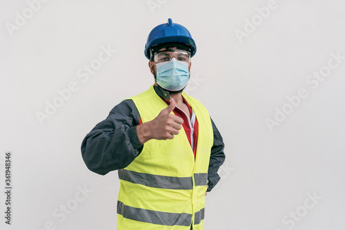 Tela Construction worker portrait on white wall posing with face mask covid -19 preve