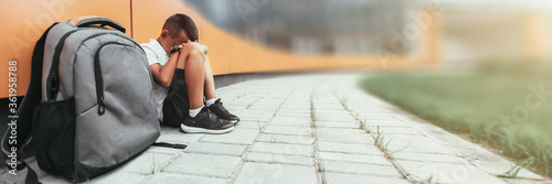 child with backpack in depression is sitting on the floor doesn't want back to school #361958788