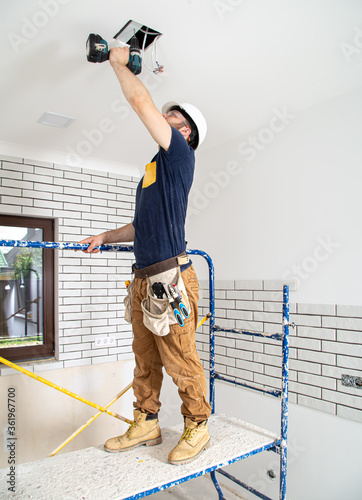 Fototapeta Electrician Builder at work, installation of lamps at height. Professional in overalls with a drill. On the background of the repair site. obraz