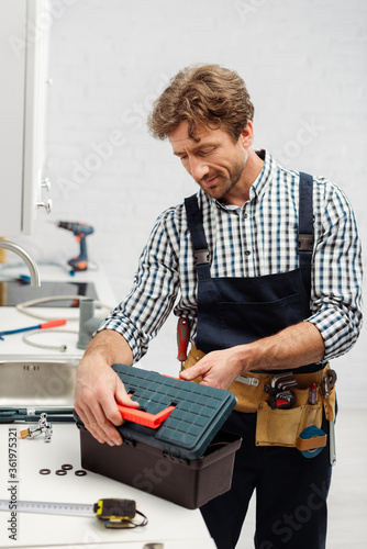 Fototapety, obrazy: Selective focus of plumber in workwear opening toolbox near tools on worktop in kitchen