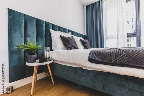 Cozy bedroom with comfortable bed in modern studio apartment. - 361977333