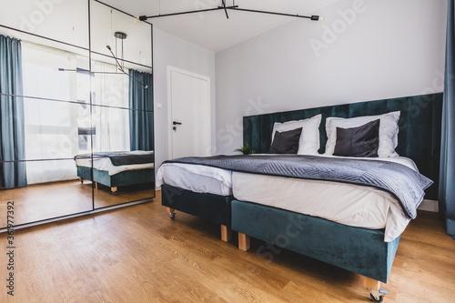 Fototapeta Cozy bedroom with comfortable bed in modern studio apartment. obraz