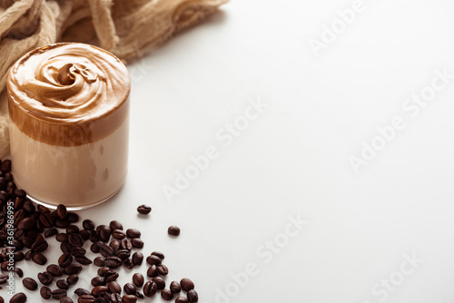 Fototapeta selective focus of delicious Dalgona coffee in glass near coffee beans and cloth on white background obraz