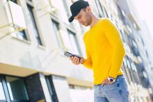Texting On A New Smartphone. A Half-length Photo Of A Young Man, Wearing Stylish Smartwatch, Standing On The Street And Texting On Hes New Smartphone.