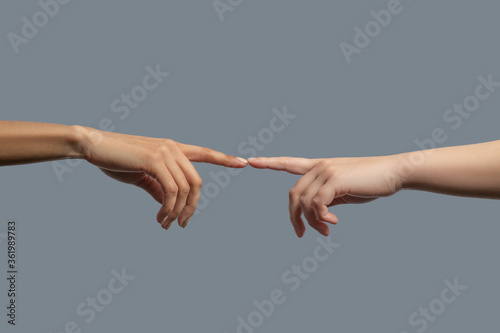 Close-up of people from different races touching two index fingers together