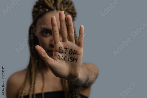 Young African American woman showing palm with stop racism lettering