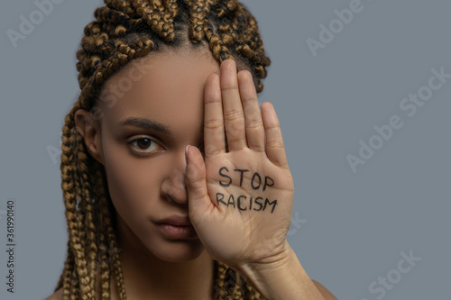 Young African American woman covering half of her face with palm with stop racism lettering
