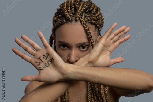 Young African American woman crossing palms with stop racism lettering