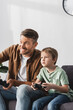 KYIV, UKRAINE - JUNE 9, 2020: excited father and son playing video game with joysticks