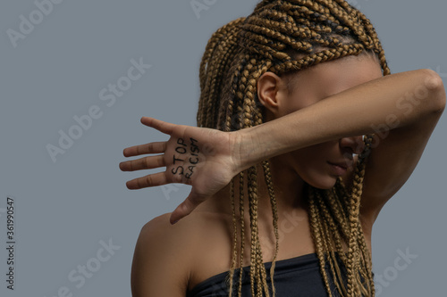 Young African American woman covering her face with elbow, showing palm with stop racism lettering