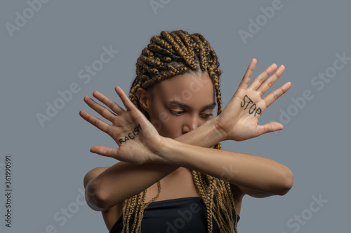 Young African American woman looking down, making cross with arms, showing palm with stop racism lettering
