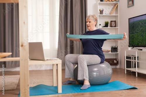 Obraz na plátne Elderly woman workout at home in front of the laptop