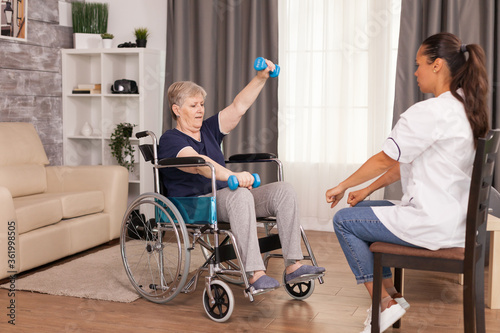 Invalid senior woman using weights with the help of nurse Canvas