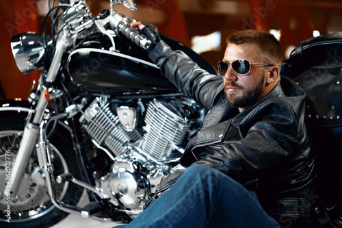 Cool man biker in sunglasses sitting near his motocycle Tablou Canvas