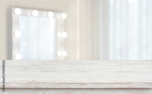 Tablou Canvas Defocused makeup mirror in dressing room with wooden table top