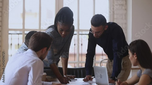 Fotografía Focused diverse business team gather at office table discuss paperwork listen af