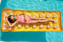 Little Girl In Sunglasses Relaxing In Swimming Pool, Enjoying Suntans, Swims On Inflatable Yellow Mattres