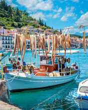 View Of Octopus Tentacles Hanging In The Sun And Traditional Fishing Boats On The Port Of Picturesque Gythio Town Greece