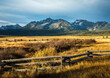 A split rail fence on the border of a large meadow with the Sawtooth mountains in the background, in the fall season near Stanley, Idaho.
