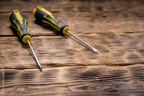 Valokuva Two screwdrivers on the wooden workbench background.