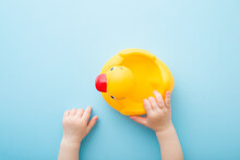 Baby Hands Touching Yellow Rubber Duck Mom On Light Blue Table Background. Pastel Color. Closeup. Bathing Toy For Little Kids. Point Of View Shot. Top Down View.