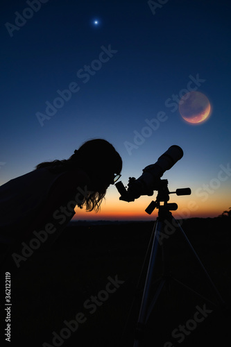 Photo Silhouette of a woman and telescope with twilight sky.
