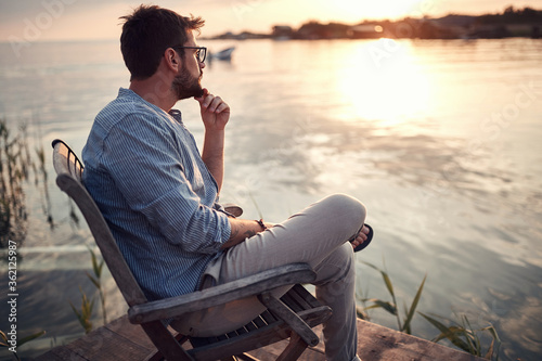 Photo beardy guy sitting alone on a river coast, enjoying the sunset, thinking