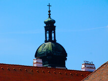 Old Copper Plated Church Clock Tower With Cross At The Top. Green Weathered Patina.. Red Clay Sloped Roof. Painted White Chimney And Metal Stacks. Clay Vents. Closeup View. Old Town Of Gyor In Hungary