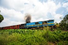 Ancien Train Coloré Avec Fumé Devant Un Champ Et Ciel Bleu