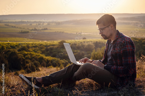 Fotografie, Obraz man with laptop sitting on the edge of a mountain with stunning views of the val