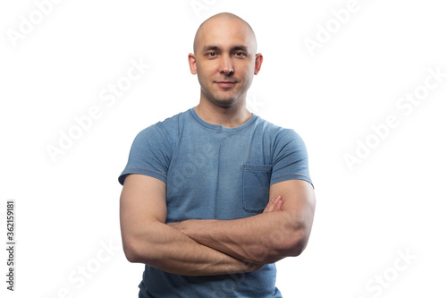 Stampa su Tela Image of young bald man with arms crossed in blue tee shirt