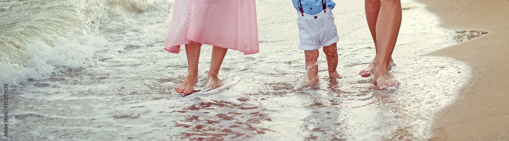 Fototapeta Family Father mother and little son walk barefoot along the seashore on the wet sand at the water's edge cropped. Summer family holidays, vacation concept