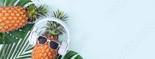 Fotografie, Obraz Funny pineapple wearing white headphone, concept of listening music, isolated on colored background with tropical palm leaves, top view, flat lay design