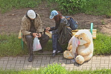 Caucasian Homeless Couple Man And Woman In Caps Sit On A Park Bench Next To A Big White Stuffed Bunny Toy A Large Plush Hare On A Summer Day, Social Issues
